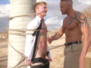 Restrained stud getting punished outdoors
