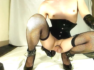 Gay crossdresser in corset with eggplant in ass