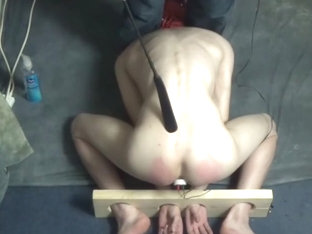 Hooded twink in the stocks with electro butt plug
